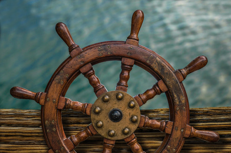 Nautical Detail Of A Ships Wheel Against Tropical Ocean Water Stock Photo