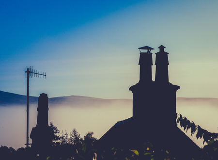pot light: Rural Rooftop And Chimney Against Misty Dusk With Copy Space Stock Photo