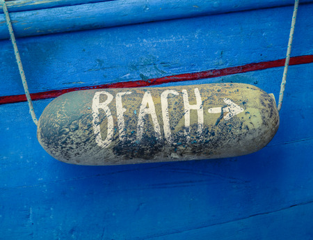 beach buoy: Retro Rustic Sign For A Beach On A Buoy On Of An Old Blue Boat