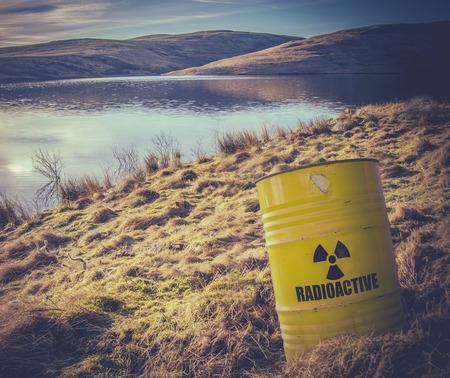 bateria musical: Una imagen conceptual de la basura nuclear del barril radiactivo o tambor cerca del agua en El Campo
