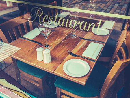 Retro Style Street Image Of A Rustic Restaurant Table Through A Window On A Cobblestone Street In Europe