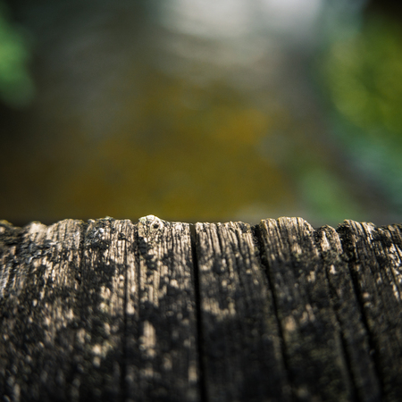 over the edge: Close-Up Of The Edge Of A Wooden Bridge Over A River With Shallow Depth Of Focus And Copy Space