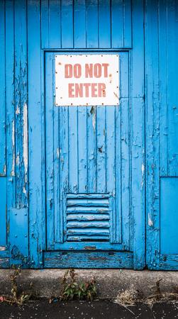 do not enter: Grungy Rustic Blue Door iIth Do Not Enter Sign Stock Photo