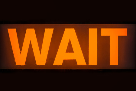 wait sign: The Glowing Orange Wait Sign At A Uk Pedestrian Crossing