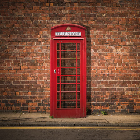 phonebooth: Grungy Traditional Red British Telephone Box Against A Red Brick Wall