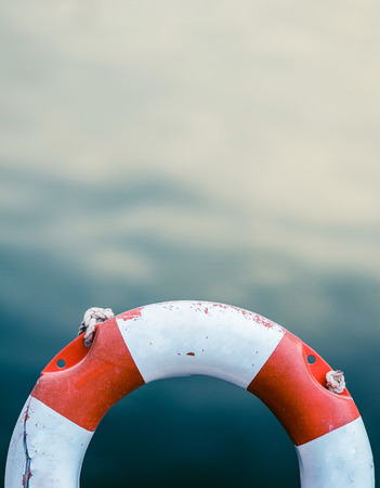 Grungy Lifebuoy Against A Calm Ocean Water Background With Copy Space