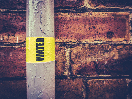 residential: Detail Of An External Residential Water Pipe Against A Red Brick Wall Stock Photo