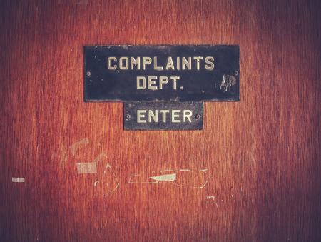ドア上の汚れた苦情部標識のレトロなフィルター処理されたイメージ