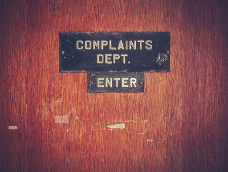 Retro gefilterde afbeelding van een grungy Klachten Afdeling Sign op een deur Stockfoto - 69659650