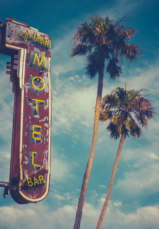 Retro Worn Vintage Neon Motel Sign And Palm Trees Stock Photo