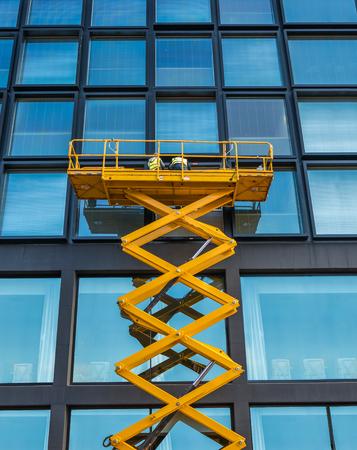 Trabajadores en un ascensor de tijera Limpieza de ventanas en un edificio financiero en el centro Foto de archivo - 86584337