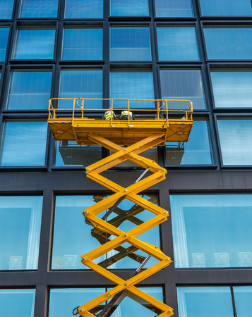 Workers On A Scissor Lift Cleaning Windows On A Financial Building Downtown