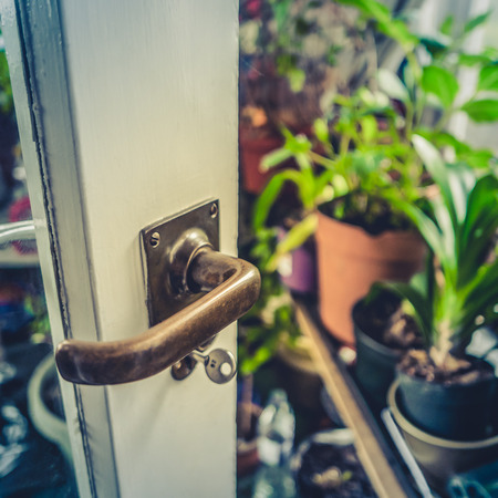 sunroom: Retro Style Detail Of A Door Opening Into A Beautiful Greenhouse Or Conservatory Stock Photo