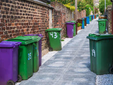 A Row Of Wheelie Bins In An Alleyway In A British City Foto de archivo