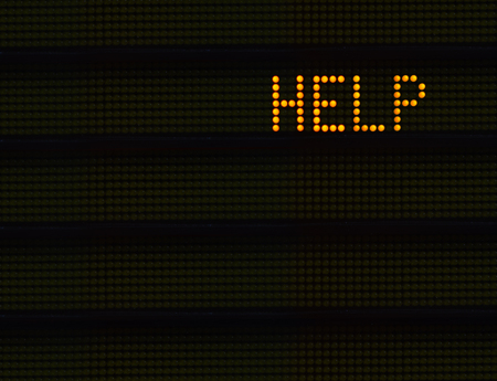 The Word HELP In Orange Lights On A Retro Signboard At An Airport Or Station Stok Fotoğraf