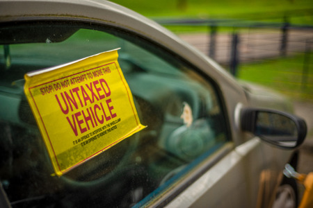 Detail Of A Warning Sign On The Window Of An Untaxed Vehicle With A Clamp On The Front Wheel Stockfoto - 106241963