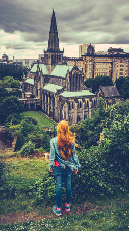 Retro Style Redhead Teenage Girl Looking Out Over Glasgow Cathedral And Skyline With A Rainy Sky 免版税图像
