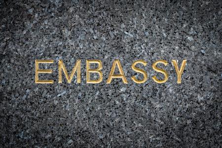 Ein goldgeprägtes Botschaftsschild auf Marmor