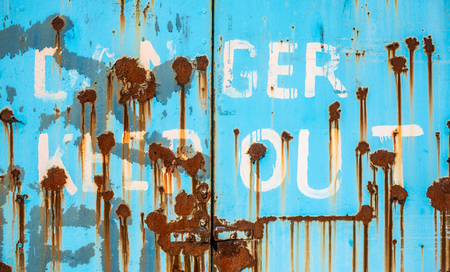 Grungy Rusty Danger Keep Out Sign Painted On To Some Heavy Industrial Doors