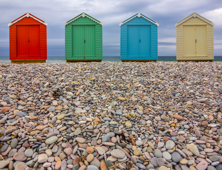 Vintage British Beach Huts On A Stony Shore With Wintry Sky With Copy Space (Focus On Foreground) Stock Photo