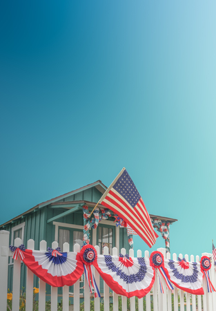 White Picket Fence USA Home With Flag And Blue Sky And Copy Space