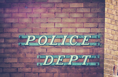 Retro Vintage Sign For A Police Department Or Station On A Red Brick Building In Small Town USA Stock Photo