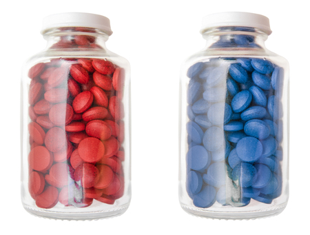 Red And Blue Pills Or Tablets In Glass Containers Isolated On A White Background