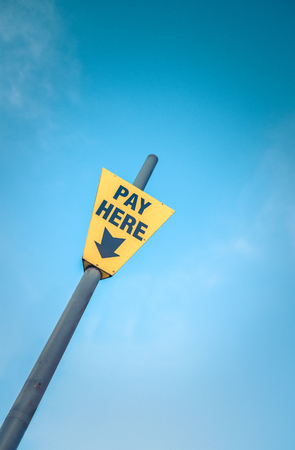 Conceptual Image Of A Bright Yellow Pay Here Sign Against A Blue Sky With Copy Space Stock Photo