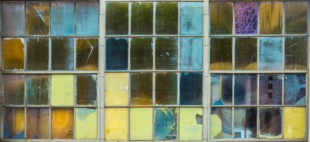 Abstract Background Of Grungy Coloured Panes Of Glass In A Factory Window