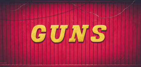 A retro red GUNS store sign. Stock Photo