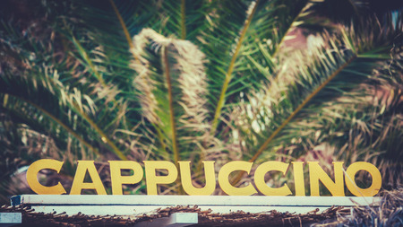 A Sign For Cappuccinos On A European Mediterranean Beach With Palm Trees Banque d'images