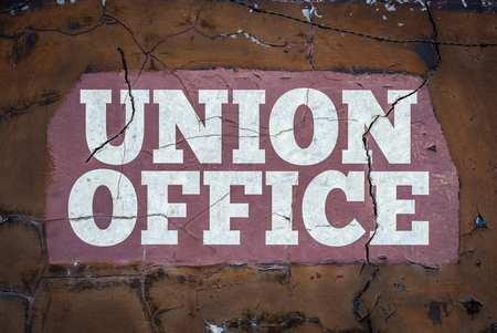 A Grungy Workers' Union Sign In Cracked White Paint At An Industrial Workplace 写真素材