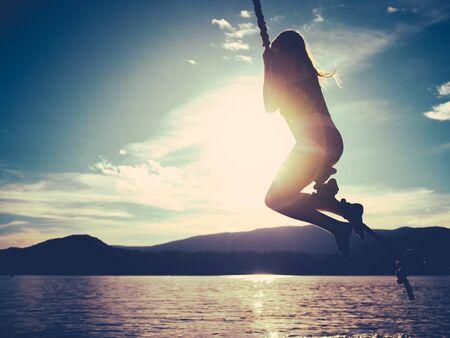 Image d'été de style rétro d'une fille se balançant dans un lac au coucher du soleil avec espace de copie