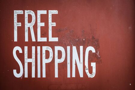 Grungy Free Shipping Sign On The Side Of A Red Metal Shipping Container 免版税图像