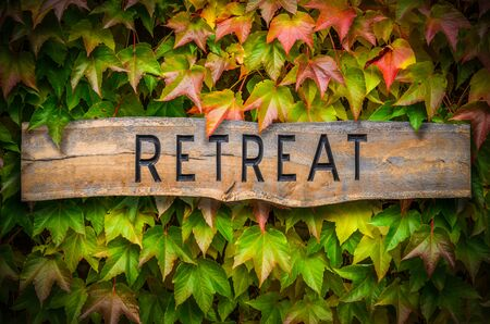 Rustic Wooden Carved Sign For A Spiritual Retreat Against A Beautiful Leafy Backdrop