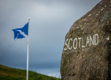 A Stone Sign At The Scottish Border With A Scotland Flag In The Distance Stockfoto
