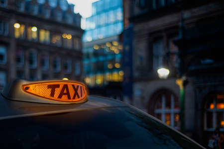 A Glowing Orange Taxi Light In A London Street At Twilight