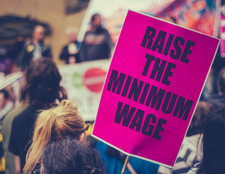 A Raise The Minimum Wage Sign At Worker's Rights Protest Or Rally