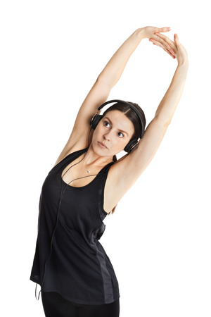 low cut: Beautiful fit caucasian girl with headphones stretching her arms up. Isolated on white background. Stock Photo
