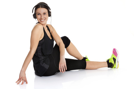 crossing legs: Beautiful fit caucasian lady with headphones stretching her body crossing legs and smiling. Isolated on white background.