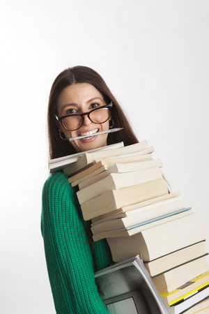 low cut: Beautiful student female with glasses holding many books and similing with a pen in her mouth. Going to study or working in a library - bookshop. Gray background.