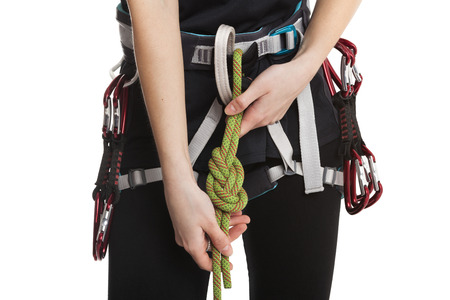 rock climbing: Beautiful rock climber girl make the safety knot before climb. Isolated on white