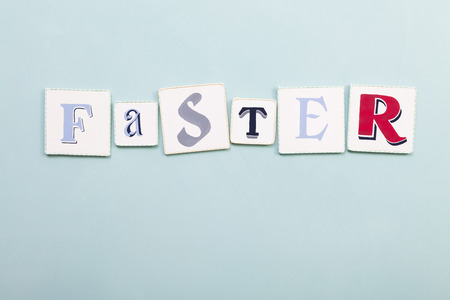 faster: Faster sign. Handwritten colors letters word. Light blue background. Calligraphy and lettering fine art. Stock Photo