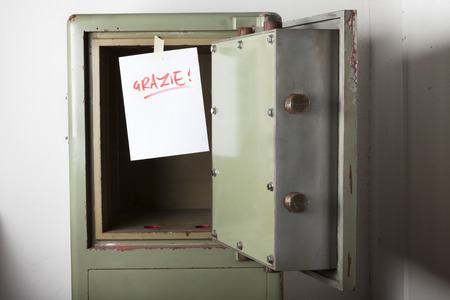 emptied: Theft. Domestic burglary. Safe box armoured emptied by thieves with message of thanks on paper: GRAZIE. Stock Photo