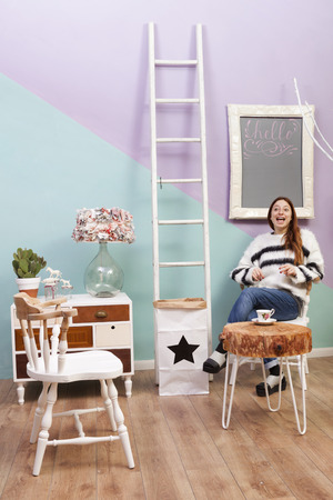sandal tree: Beautiful redhead girl at cafe drinking and sitting under a white framed hello blackboard. Design furniture and accesories. Paper bin with star. Colored background and white ladder. Stock Photo