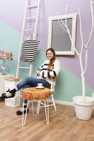 Beautiful redhead girl at cafe drinking and sitting under a white framed hello blackboard. Design furniture and accesories. Paper bin with star. Colored background and white ladder. photo
