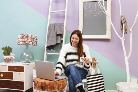 Redhead girl fashion blogger working at cafe with laptop drinking a cup of tea. Striped shopping bag. Design furniture and accesories. Colored background and white ladder hanger. photo