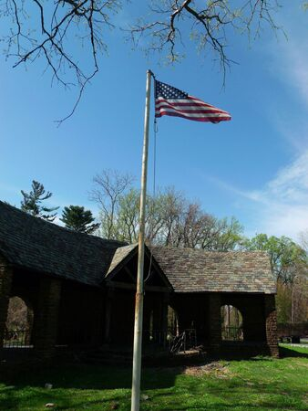 American flag, high atop flag pole, waving in the breeze in front of building in Druid Hill Park (Baltimore,MD). Banco de Imagens