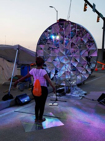 Middle-aged, African-American woman, interacting with solar-powered device at Artscape; located in Baltimore,MD.