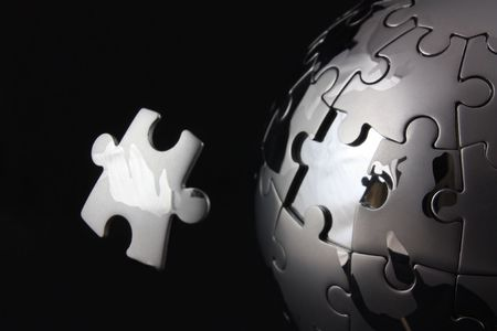 final piece of the puzzle: Floating jigsaw peice over chrome puzzle globe Stock Photo